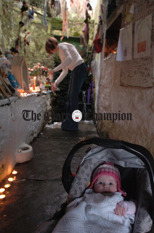 Baby Leah Scanlan waits for her mother Mary to collect holy water at the St Brigids Well grotto, Liscannor, on the feast day of St Brigid. Photograph by John Kelly.