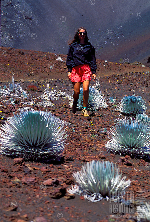 Woman hiking through Haleakala National park near silversword plants, Maui