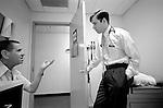 Elderly male patient gestures to listening doctor in examination room