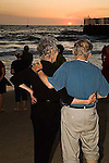 Mature man and woman with gray hair stand on beach holding arms around each other looking at sunset with other people at dusk at Playa del Rey beach in Los Angeles, California