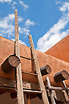 Looking up at a ladder and adobe walls inside the courtyard of the Rainbow Man store