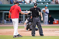 Umpire Adam Pierce gets a water break during a game between the Asheville Tourists and Greenville Drive on Tuesday, June 1, 2021, at Fluor Field at the West End in Greenville, South Carolina. (Tom Priddy/Four Seam Images)