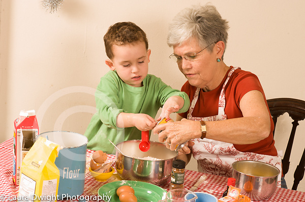 3 year old boy cooking baking activity with grandmother Caucasian modeling imitation stirring his own bowl as grandmother stirs hers horizontal looking and observing how she stirs