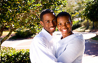 Black African American couple happy together in sunshine at home together in yard and snuggling