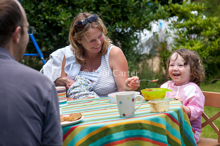 A young mother breastfeeds her new baby whilst feeding her toddler soup with a spoon at the same time at a table in the garden on a summer's day.<br /> <br /> 26/08/12<br /> Hampshire, England, UK