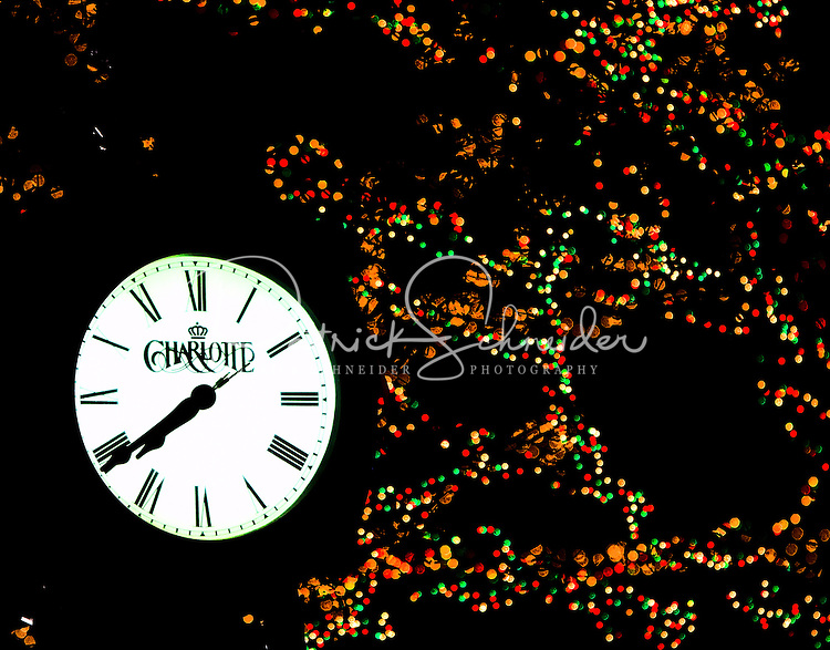 Holiday / Christmas lights glow in colorful reds, greens and whites behind the iconic Charlotte clock in downtown / uptown / center city Charlotte. Photo taken as part of a series of images that capture holiday decorations and festivities in and around Charlotte by Charlotte photographer Patrick Schneider.