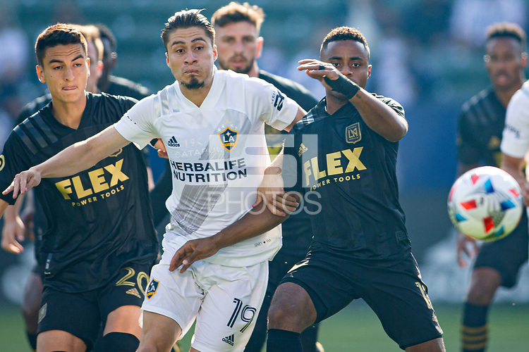 CARSON, CA - MAY 8: Eduard Atuesta #20 and Diego Palacios #12 of LAFC battle with Jorge Villafana #19 of the Los Angeles Galaxy during a game between Los Angeles FC and Los Angeles Galaxy at Dignity Health Sports Park on May 8, 2021 in Carson, California.