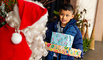 NAUGATUCK,  CT-122519JS07- Derek Bermudez, 7, of Naugatuck, thanks Santa for his gifts he received during the annual Christmas Day Dinner at St. Michael's Church in Naugatuck on Wednesday. The dinner, which as been a tradition for over 30 years, was started by Naugatuck resident John Ford and his late wife Maureen, to show their children the true meaning of Christmas. The event is now run by Jim and Susan Goggin. <br /> Jim Shannon Republican-American