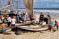 Brazilian fishermen (jangadeiros) work on the beach of Iguape, Ceará state, northeastern Brazil, 14 March 2004. Jangadeiros, working on a unique wooden raft boat called jangada, keep the tradition of artisan fishing for more than four hundred years. However, being a fisherman on jangada is highly dangerous job. Jangadeiros spend up to several days on high-sea, sailing tens of kilometres far from the coast, with no navigation on board. In the last two decades jangadeiros have been facing up the pressure from motorized vessels which use modern, effective (and environmentally destructive) fishing methods. Every time jangadeiros come back from the sea with less fish.