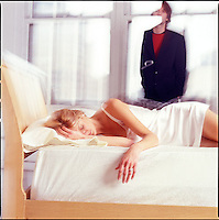 Woman in bed with man in background against windows<br />