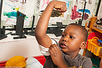 Education Preschool 3-4 year olds boy showing off his arm muscle