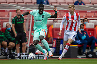 11th September 2021;  Bet365 Stadium, Stoke, Staffordshire, England; EFL Championship football, Stoke City versus Huddersfield Town; Naby Sarr of Huddersfield Town holds up the ball under pressure from  Sam Surridge of Stoke City