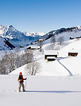 Switzerland, Canton Uri, Urigen: mountain village at Schaechen Valley and Swiss Central Alps - woman hiking in deep snow