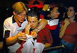 English football fans World Cup 1998. Supporters show their disappointment and disbelief. Tears from one young fan and a loving arm of friendship and support from another at loosing to Argentina in a penalty shoot out. And thus getting knocked out of the World Cup. Watching on a multi screens in a television room of the Sports Bar, London 1990s UK