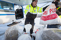 Volunteer Iditarod Air Force pilot, Greg Fischer loads hay, musher drop bags, people food and HEET into his plane at the Willow, Alaska airport during the Food Flyout on Saturday, February 20, 2016.  Iditarod 2016