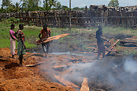 MOZAMBIQUE, Beira, timber trade of chinese company, storage place for logged trees from Tete province, after sawing the timber boards are packed in Container and shipped from Beira port to China, local people make charcoal from the remains of chinese sawmill / MOSAMBIK, Beira, Holzhandel der chinesischer Firmen, Lagerplatz fuer Baumstaemme aus der Provinz Tete, zugesaegte Hoelzer werden in Container verpackt und ueber den Hafen Beira nach China verschifft, Kahlschlag in Mosambik, taeglich kommen hunderte Lastwagen mit Holz in Beira an, fuer die lokale Bevoelkerung bleiben die Saegereste fuer Holzkohle