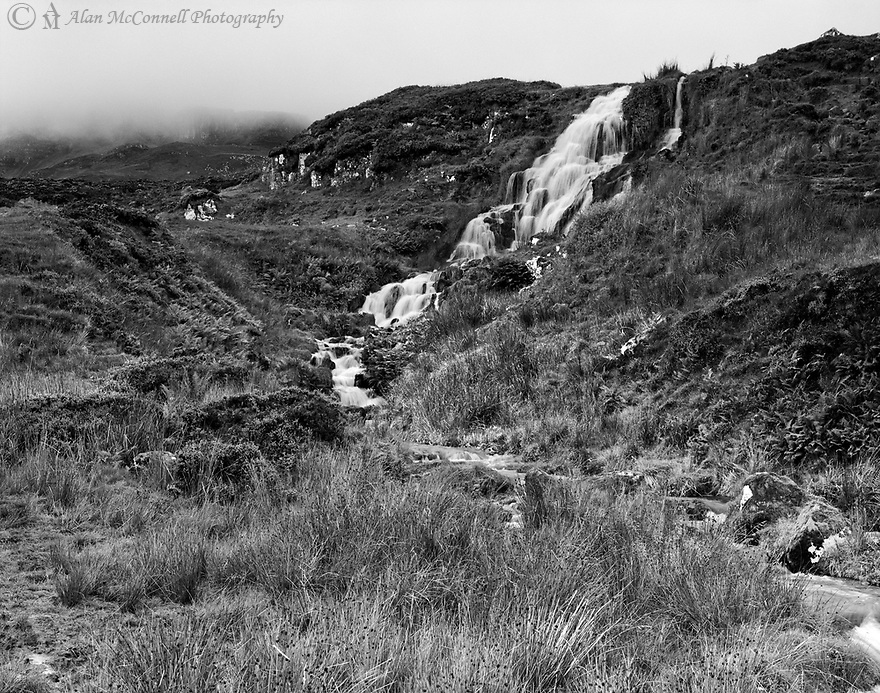 An early morning mist descends from the hills of the Isle of Skye to a small cascade called Bride's Veil Falls.  Nourishing the soft peaty soil, the water travels a short distance to Loch Leathan and then to the North Sea.