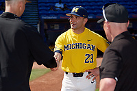 Michigan Wolverines head coach Erik Bakich (23) shakes hands with Army head coach Jim Foster during the lineup exchange before a game on February 17, 2018 at Tradition Field in St. Lucie, Florida.  Army defeated Michigan 4-3.  (Mike Janes/Four Seam Images)