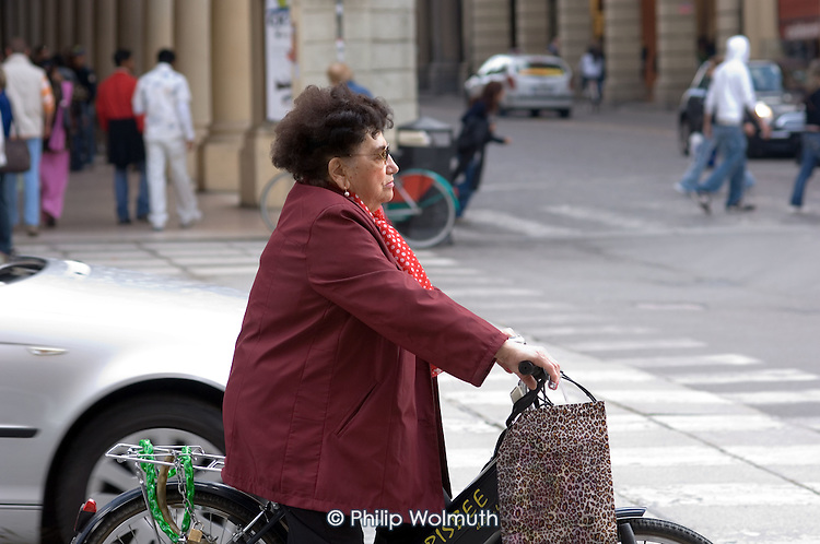 An elderly woman on a bicycle in Bologna