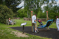 A mother  breastfeeding her child during a family outing to a local park and gardens. She is watching her husband play with her older boy on a swing.<br /> <br /> 11-06-2015<br /> Hampshire, England, UK<br /> <br /> © Paul Carter / wdiip.co.uk