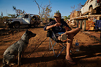 Joanna Atkins has lunch, with dog Lin, after setting up a temporary work camp on the side of the Gibb River Road, as she travels with husband Nick in their road train from Kununurra to Kalumburu.
