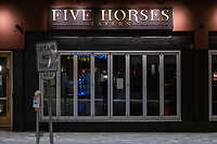 """A sign in the window of Five Horses Tavern in Davis Square reads """"We have decided to temporarily pause all operations and plan on reopening in March,"""" due to the ongoing Coronavirus (COVID-19) global pandemic in Somerville, Massachusetts, on Tue., Jan. 26, 2021."""