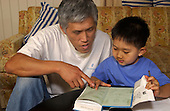 MR/Schenectady, NY / .Father (Korean-American) works with son at table with book, paper, and pencil..MR: Kim2 Kim5.©Ellen B. Senisi