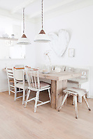 The kitchen table was made from salvaged wood and works well with the worn, natural quality of the chairs grouped around it