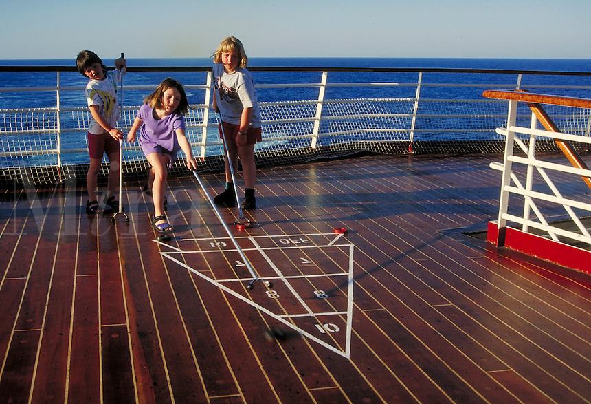 """children playing shuffleboard on the deck on """"Song of America"""" cruise ship. children."""