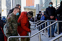 NEW YORK, NEW YORK - MARCH 02: A military member helps an elderly man to enter the Javits Center to receive a vaccine against the Coronavirus on March 2, 2021 in New York. Long wait times were reported at Manhattan's Javits Center vaccination with a long line of people extending outside and around the block. (Photo by Emaz/VIEWpress)