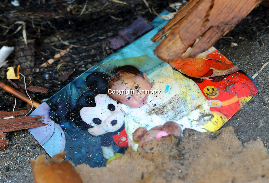 A photo of a baby lies amongst the wreckage near Sendai.  Personal belongs were the greatest loss with people returning looking for momentos of loved ones lost photo albums, pictures and family heirlooms. .16 Mar 2011