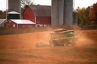 A tractor harvesting in a farm field beyond a barn and silo. Wisconsin.