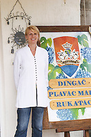 Mrs Matusko, from Germany, married to Mato Violic Matusko, the winemaker, outside the winery with a sign with the wine names and the coat of arms with a crown, two donkeys' heads bunch of grapes. Matusko Winery. Potomje village, Dingac wine region, Peljesac peninsula. Matusko Winery. Dingac village and region. Peljesac peninsula. Dalmatian Coast, Croatia, Europe.