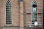 Foto: VidiPhoto<br /> <br /> IJZENDOORN – Schilders en restaurateurs werken maandag aan de buitenzijde van de Hervormde kerk (14e eeuw) in IJzendoorn in de Betuwe. De drie grote ramen aan de Waalzijde van de kerk zijn vernieuwd. Doordat een aantal ruitjes in de ramen te klein bleken, worden deze nu vervangen. Aan diezelfde zuidkant wordt nieuw voegwerk aangebracht. Volgend jaar worden de daklijsten en watergoten vervangen. Al eerder werden de leistenen op het dak vernieuwd. Het grootste deel van de restauratiekosten van ruim 120.000 euro wordt betaald uit cultuur- en monumentenfondsen.