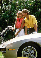 A young couple laughs and washes a car together.