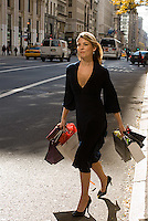 Young blonde woman carrying gift bags walking across the street