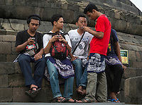 Borobudur, Java, Indonesia.  Young Indonesian Men Checking their Cell Phones while Visiting the Temple.