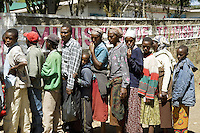 Kenya. Rift Valley province. Nakuru. 25.01.2008. Show Ground. A group of black Kikuyu men, women and children stand on line. They are all Internally displaced persons (IDPs) forced to flee their homes because of the inter-ethnic strife, but who, unlike refugees, remain within their country's borders. Mural painting with the words: Ministry of Tourism. The Kikuyus are Kenya's most populous ethnic group.  © 2008 Didier Ruef