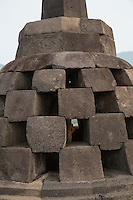 Borobudur, Java, Indonesia.   Close-up of a stupa on the upper level of the temple.  The square-shaped holes symbolize the overcoming of passions as one approaches Nirvana.