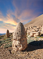 Statue head at sunset of Zeus & Antiocchus behind, in front of the 62 BC Royal Tomb of King Antiochus I Theos of Commagene, west Terrace, Mount Nemrut or Nemrud Dagi summit, near Adıyaman, Turkey