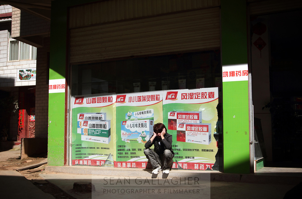 CHINA. A man outside a storefront in Zijun village in Kunming, home of the Samatao minority. 2010