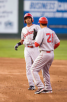 Spokane Indians outfielder Christopher Garia #1 hands his leg guard to coach Vinny Lopez #21 after hitting a double against the Everett AquaSox at Everett Memorial Stadium on June 20, 2012 in Everett, WA.  Everett defeated Spokane 9-8 in 13 innings.  (Ronnie Allen/Four Seam Images)