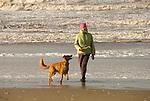 Woman with a Golden Retriever on the beach, Oregon Coast