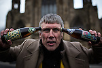 """© Joel Goodman - 07973 332324 .  12/01/2015 . Salford , UK . BEZ ( Mark Berry ) poses with """" Frack Free """" beer in front of Salford Cathedral at the launch of his parliamentary campaign for the constituency of Salford and Eccles at a poster site on Chapel Street , Salford . Bez , the freaky dancer from Madchester band The Happy Mondays , is standing for The Reality Party . Seat incumbent , Labour's Hazel Blears , is standing down at the 2015 election . Photo credit : Joel Goodman"""