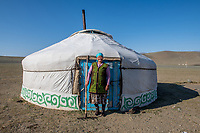 Mongolia, Bayan-Ulgii, Ulgii, Altai Mountains. Family in their yurt near Tsambagarav Mountain. Kazakh woman outside her yurt,