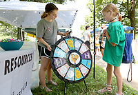 Shelby Haynes, 11, is assisted by Cassidy Waide (cq), a volunteer at the City of Fayetteville Community Resources booth, Friday, July 30, 2021, as she spins a wheel for a prize during the annual CDBG in the Park picnic at Walker Park in Fayetteville. The city's Community Development Block Grant program received $748,785 from the federal government this year and pays for a variety of programs, including housing rehabilitation, taxi passes, Ranger's Pantry AniMeals and the Hearth program to house residents. Check out nwaonline.com/210731Daily/ and nwadg.com/photos for a photo gallery.(NWA Democrat-Gazette/David Gottschalk)