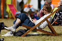 Pictured: Festival goers lounge on the festival green. Friday 31 May 2019<br /> Re: Hay Festival, Hay on Wye, Wales, UK.