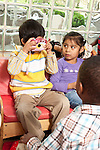 Education Preschool pretend play 3-4 year olds boy taking picture of another child as girl watches