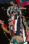Lima, Peru. Man wearing a heavily embroidered jacket and a beaded mask ringing a bell at the Independence Day festival.