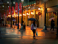 Urban Street Photograph of an early morning rain. Office workers on the way to work.